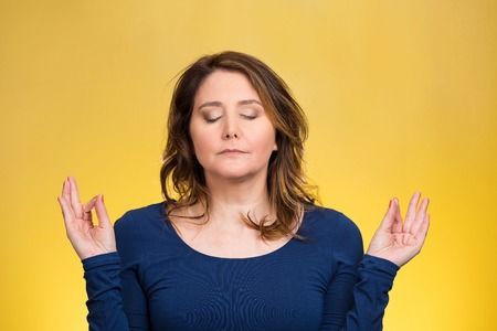 Closeup portrait peaceful young woman relaxing, meditating, in zen mode, isolated yellow background. Positive human emotions, facial expressions, attitude, life perception, situation, symbols, approach photo
