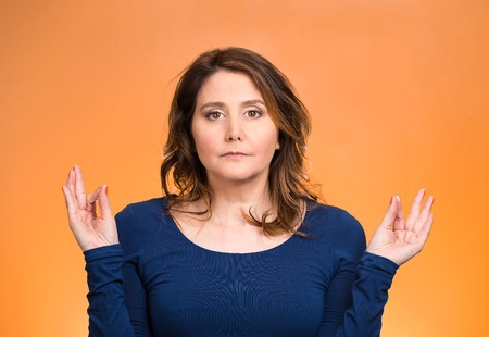 Closeup portrait peaceful young woman relaxing, meditating, in zen mode, isolated orange background. Positive human emotions, facial expressions, attitude, life perception, situation, symbols, approach photo