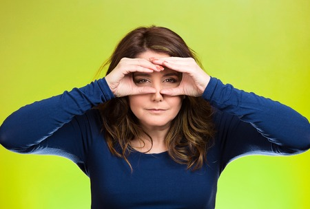 forcast: Closeup portrait young, curious funny woman, looking through fingers like binoculars, searching something, unhappy with what waiting in future isolated green background. Facial expression, body language