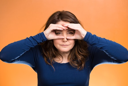 forcast: Closeup portrait young, curious funny woman, looking through fingers like binoculars, searching something, unhappy with what waiting in future isolated orange background. Facial expression, body language Stock Photo