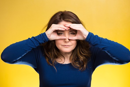 forcast: Closeup portrait young, curious funny woman, looking through fingers like binoculars, searching something, unhappy with what waiting in future isolated yellow background. Facial expression, body language
