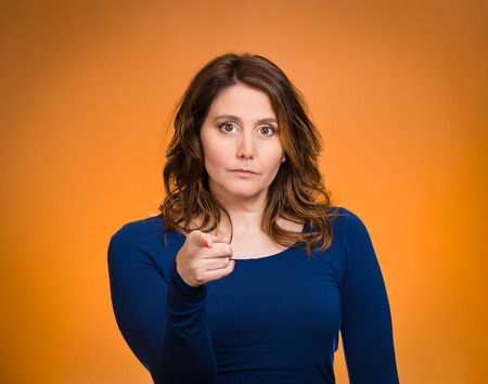 Portrait young, unhappy, serious woman pointing finger at someone, blaming for something wrong, mistake, isolated orange background. Negative human emotions, facial expressions, feelings, reaction