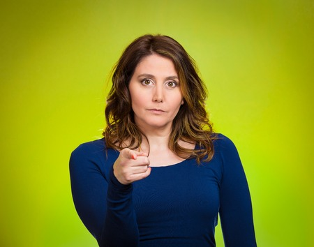 Portrait young, unhappy, serious woman pointing finger at someone, blaming for something wrong, mistake, isolated green background. Negative human emotions, facial expressions, feelings, reaction Stock Photo