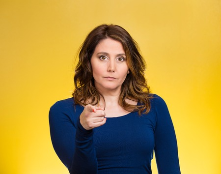 Portrait young, unhappy, serious woman pointing finger at someone, blaming for something wrong, mistake, isolated yellow background. Negative human emotions, facial expressions, feelings, reaction