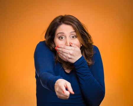 blown away: Portrait middle aged woman pointing with index finger, laughting, stunned, dumbstruck, dumbfounded, looking surprised, covering mouth isolated orange background. Human emotion, facial expression, feelings Stock Photo