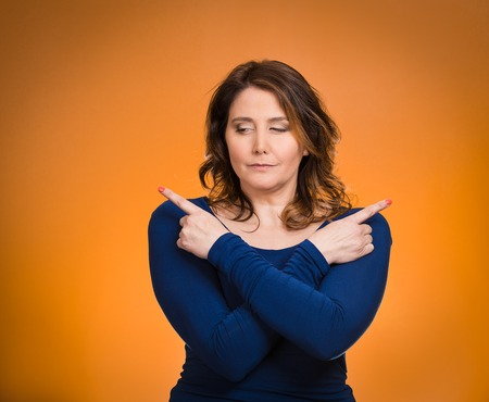 befuddled: Portrait confused young woman pointing with fingers in two different directions, not sure which way to go in life, isolated orange background. Human emotions, facial expressions, feeling, body language