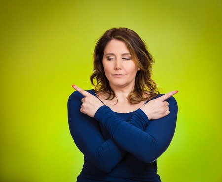befuddled: Portrait confused young woman pointing with fingers in two different directions, not sure which way to go in life, isolated green background. Human emotions, facial expressions, feeling, body language