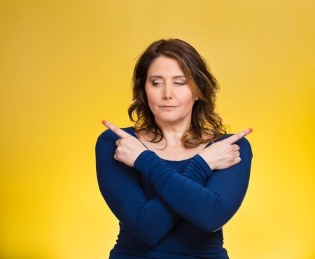 disorganized: Portrait confused young woman pointing with fingers in two different directions, not sure which way to go in life, isolated yellow background. Human emotions, facial expressions, feeling, body language Stock Photo