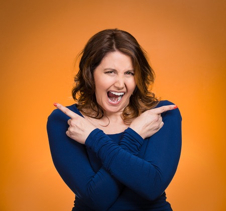 Portrait confused young woman pointing in two different\ directions, stressed, frustrated, screaming, overwhlemed, not sure\ which way to go in life isolated orange background. Negative\ emotion facial expression feeling body language