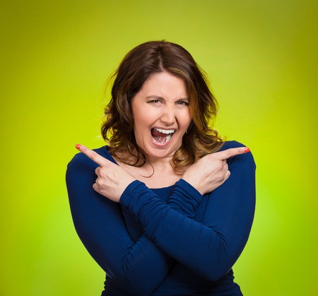 which way: Portrait confused young woman pointing in two different directions, stressed, frustrated, screaming, overwhlemed, not sure which way to go in life isolated green background. Negative emotion facial expression feeling body language Stock Photo