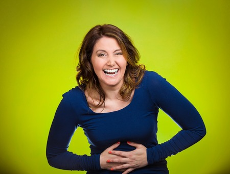 mirth: Portrait young, smiling, happy, laughing woman hearing good news, joke hands on stomach, looking at camera isolated green background. Positive human emotions, facial expressions, reaction, attitude