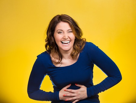 mirth: Portrait young, smiling, happy, laughing woman hearing good news, joke hands on stomach, looking at camera isolated yellow background. Positive human emotions, facial expressions, reaction, attitude