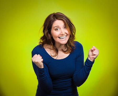 jubilate: Closeup portrait winning successful young business woman happy ecstatic celebrating being winner isolated green background. Positive human emotion facial expression, attitude Life achievement concept