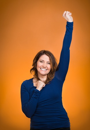 jubilate: Closeup portrait winning successful young business woman happy ecstatic celebrating being winner isolated orange background. Positive human emotion facial expression, attitude Life achievement concept Stock Photo