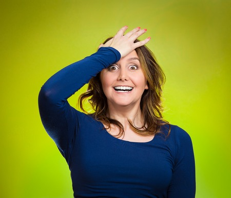 Closeup portrait excited middle aged woman placing hand on head, palm on face gesture in duh moment, isolated green background. Human emotion facial expression feelings, body language, reaction photo