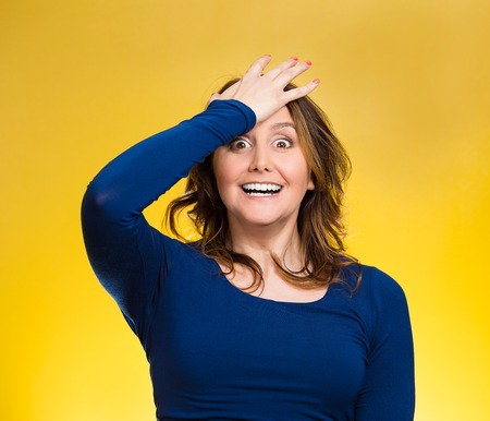 duh: Closeup portrait excited middle aged woman placing hand on head, palm on face gesture in duh moment, isolated yelllow background. Human emotion facial expression feelings, body language, reaction Stock Photo