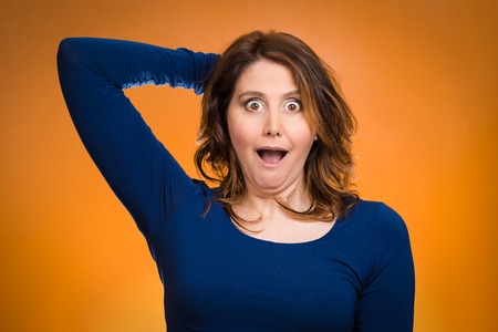 Closeup portrait, headshot startled woman, looking shocked, surprised, hands in air, unexpected situation isolated orange background. Human emotion, facial expressions, feelings, reaction disbelief
