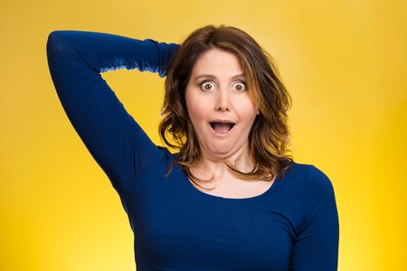 fear face: Closeup portrait, headshot startled woman, looking shocked, surprised, hands in air, unexpected situation isolated yellow background. Human emotion, facial expressions, feelings, reaction disbelief