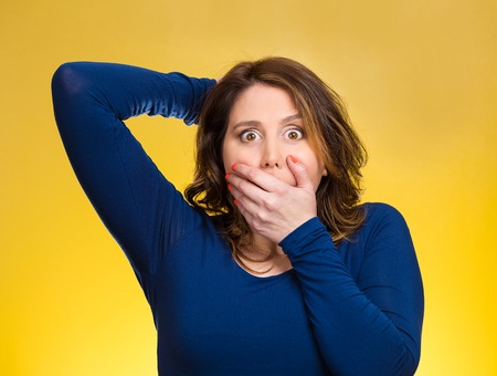 blown away: Closeup portrait, headshot startled woman, looking shocked, surprised, covering mouth with hand, unexpected situation isolated yellow background. Human emotion, facial expression feeling reaction disbelief Stock Photo