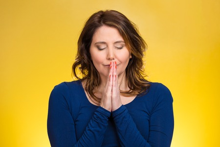 woman praying: Closeup portrait young woman praying, eyes closed, calm, hoping for best in future, asking forgiveness, miracle isolated yellow background. Human emotions, facial expression, feelings, life perception
