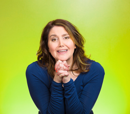 solicit: Closeup portrait young woman gesturing with clasped hands, pretty please with sugar on top, isolated green background. Positive emotions, facial expressions, feelings, signs symbols, body language