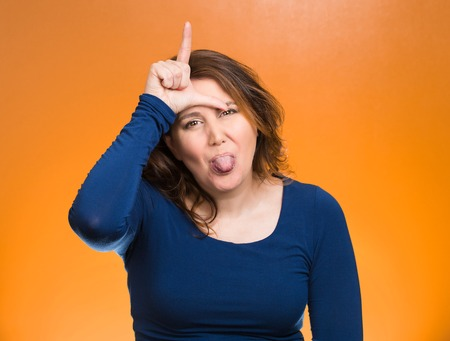 insulting: Closeup portrait angry, mad pissed woman, showing loser sign, sticking tongue out, hand on forehead, isolated orange background. Negative emotion facial expression signs symbol feelings body language Stock Photo
