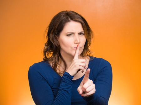 cranky: Closeup portrait, serious mature woman placing finger, hand on lips, shhh gesture, be quiet, silence, isolated orange background. Negative facial expression, sign, emotion, feelings, body language Stock Photo