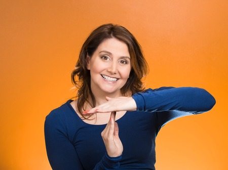 hands out: Closeup portrait, young, happy, smiling woman showing time out gesture with hands, isolated orange background. Positive human emotions, facial expressions, feelings, body language, reaction, attitude