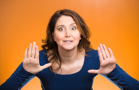 disrespect: Portrait cautious, afraid, annoyed displeased young woman raising hands up to say no, stop right there isolated orange background. Negative human emotion facial expression sign symbol