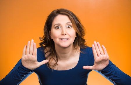 irrespeto: Retrato cauteloso, con miedo, molesto disgustado mujer joven levantando las manos para decir que no, tiene que parar allí aislado fondo naranja. Emoción humana Negativo expresión facial símbolo