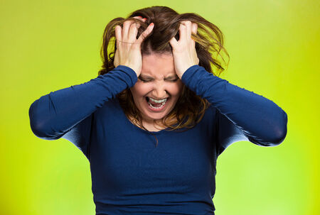 going crazy: Closeup portrait stressed business woman, pulling her hair out, yelling, screaming with temper tantrum isolated green background. Negative human emotions, facial expressions, reaction attitude Stock Photo