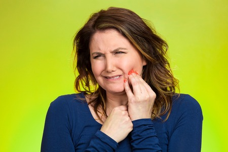 Portrait middle aged woman with sensitive tooth ache, crown problem crying from pain, touching outside mouth with hand isolated green background. Negative emotion, facial expression feeling, health photo