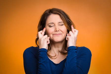 crossing fingers: Closeup portrait hopeful beautiful woman, mother crossing her fingers, hoping asking for best isolated orange background. Human face expression, emotion feeling attitude reaction, body language