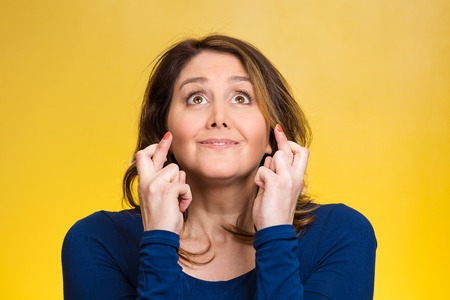restless: Closeup portrait hopeful beautiful woman, mother crossing her fingers, hoping asking for best isolated yellow background. Human face expression, emotion feeling attitude reaction, body language