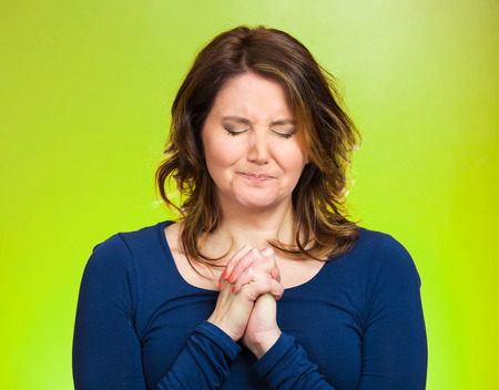 hoping: Closeup portrait young woman praying, eyes closed, calm, hoping for best in future, asking forgiveness, miracle isolated green background. Human emotions, facial expression, feelings, life perception