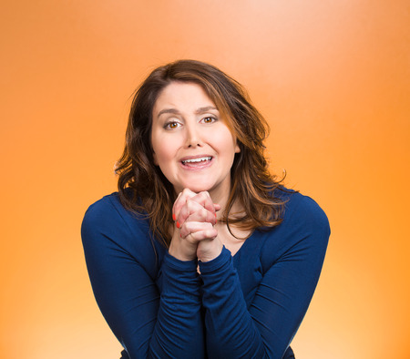 solicit: Closeup portrait young woman gesturing with clasped hands, pretty please with sugar on top, isolated orange background. Positive emotions, facial expressions, feelings, signs symbols, body language Stock Photo