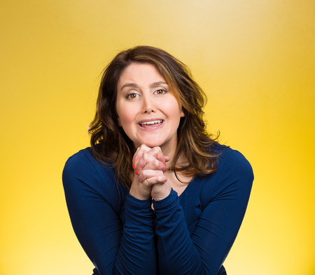 solicit: Closeup portrait young woman gesturing with clasped hands, pretty please with sugar on top, isolated yellow background. Positive emotions, facial expressions, feelings, signs symbols, body language