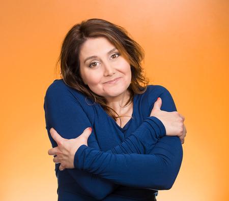 ego�sta: Primer retrato feliz sonriente mujer, tenencia, abraz�ndose a s� misma, fondo naranja aislado. La emoci�n positiva humana, la expresi�n facial, el sentimiento, reacci�n, situaci�n actitud. Vida amarte a ti mismo concepto