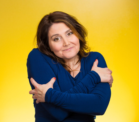 egoist: Closeup portrait happy smiling woman, holding, hugging herself, isolated yellow background. Positive human emotion, facial expression, feeling, reaction, situation attitude. Life love yourself concept