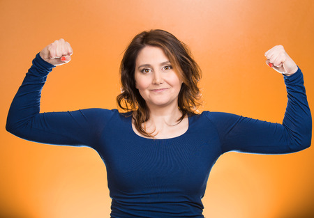 weight loss plan: Closeup portrait beautiful, pretty model woman flexing muscles showing, displaying her strength, isolated orange background. Positive human emotions, facial expressions, feelings, attitude, perception