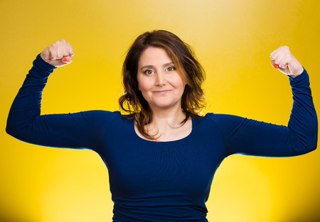 diet plan: Closeup portrait beautiful, pretty model woman flexing muscles showing, displaying her strength, isolated yellow background. Positive human emotions, facial expressions, feelings, attitude, perception Stock Photo