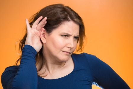 chitchat: Closeup portrait curious young nosy, funny looking woman, hand to ear trying to carefully, intently, secretly listen in on juicy gossip conversation, news, privacy violation isolated orange background Stock Photo