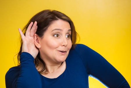 Closeup portrait curious, nosy woman listening to someones conversation, hand to ear gesture,  looking surprised shocked by what she discovered isolated yellow background. Human emotion expression photo