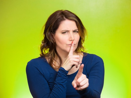 Closeup portrait, serious mature woman placing finger, hand on lips, shhh gesture, be quiet, silence, isolated green background. Negative facial expression, sign, emotion, feelings, body language photo