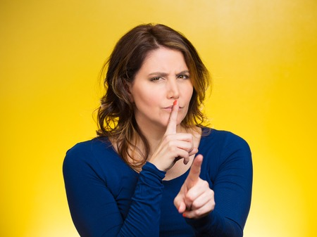 placing: Closeup portrait, serious mature woman placing finger, hand on lips, shhh gesture, be quiet, silence, isolated yellow background. Negative facial expression, sign, emotion, feelings, body language