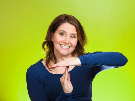 reasonable: Closeup portrait, young, happy, smiling woman showing time out gesture with hands, isolated green background. Positive human emotions, facial expressions, feelings, body language, reaction, attitude