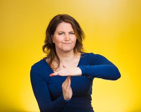 business skeptical: Primer retrato, edad media infeliz, mujer seria que muestra el tiempo en gesto con las manos aisladas fondo amarillo. La emoci�n negativa humana, la expresi�n facial, s�mbolo, el lenguaje corporal, la actitud