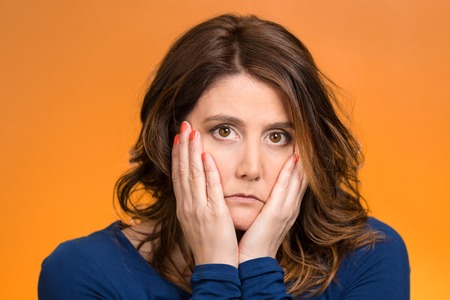 Closeup portrait sad, depressed, stressed, thoughtful middle aged woman, full of worries, confused, lost isolated orange background. Human face expressions, emotions, feeling reaction attitude, body language photo