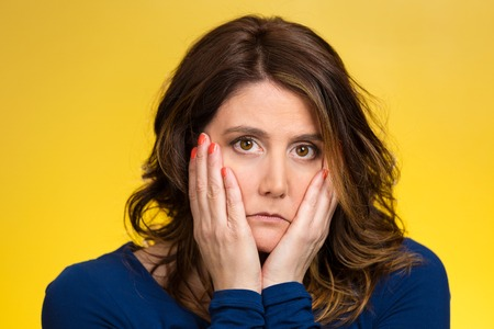 Closeup portrait sad, depressed, stressed, thoughtful middle aged woman, full of worries, confused, lost isolated yellow background. Human face expressions, emotions, feeling reaction attitude, body language photo