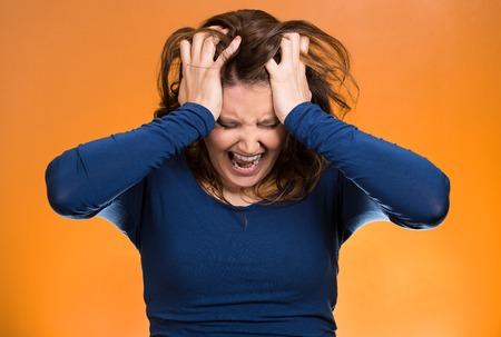 stupor: Retrato del primer subray� mujer de negocios, tirando de sus cabellos, gritando, gritando con rabieta aislado fondo naranja. Emociones humanas negativas, las expresiones faciales, la actitud de reacci�n Foto de archivo